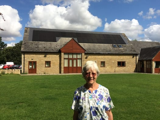 Celia Hawkesworth of Sustainable Kirtlington, standing outside Kirtlington Village Hall with its solar panels installed