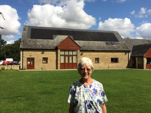 Celia Hawkesworth of Sustainable Kirtlington, standing outside Kirtlington Village Hall with its solar panels installed