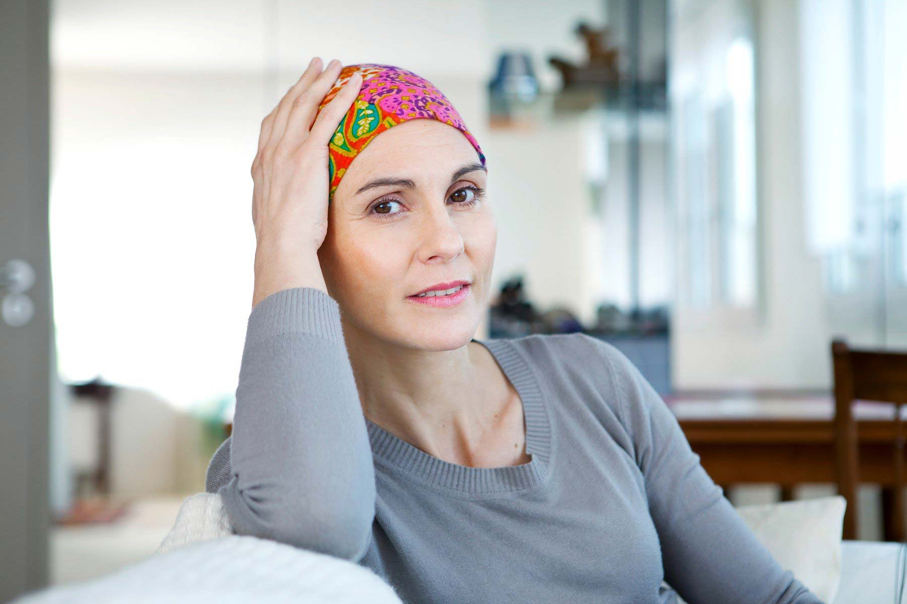 Cancer Center - woman holding her hand on head with scarf