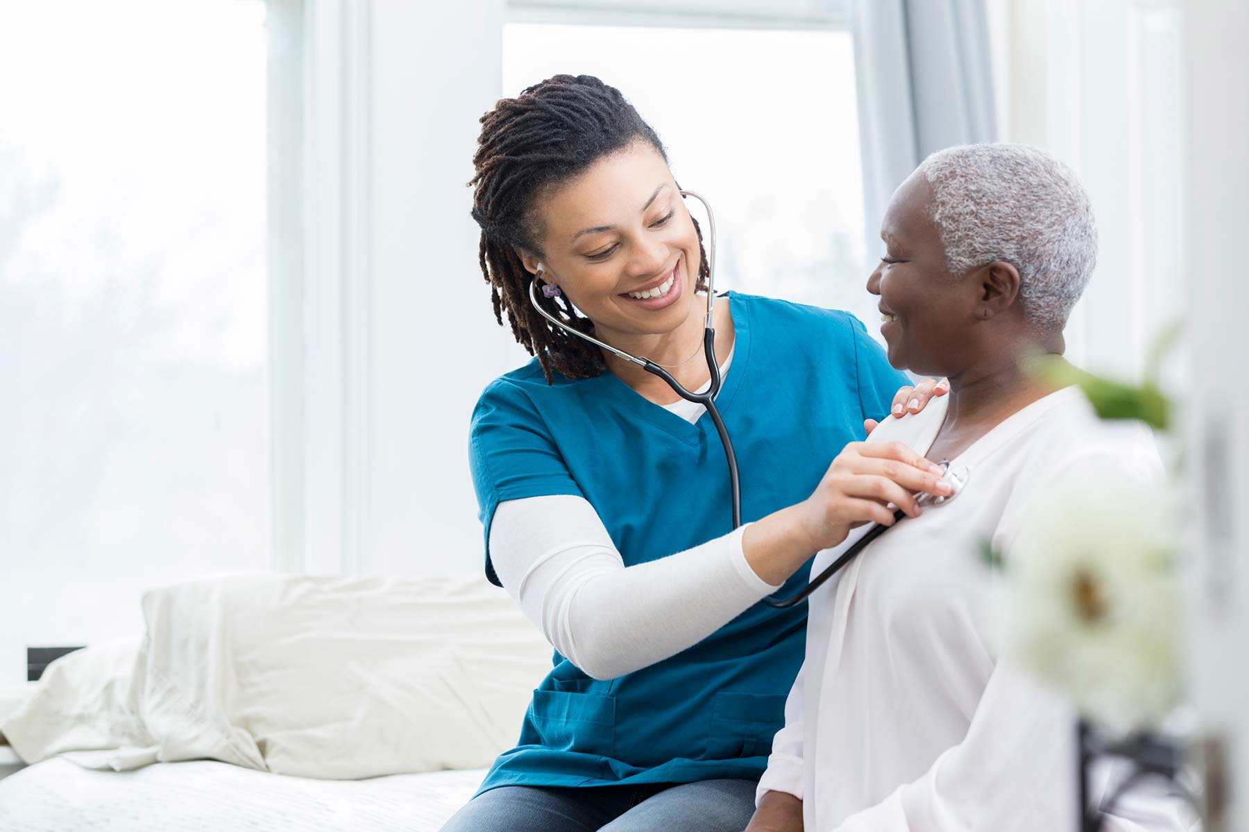 Home Care - provider checking patient with stethoscope