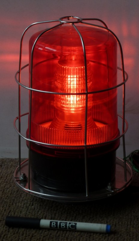 Caged red industrial warning beacon