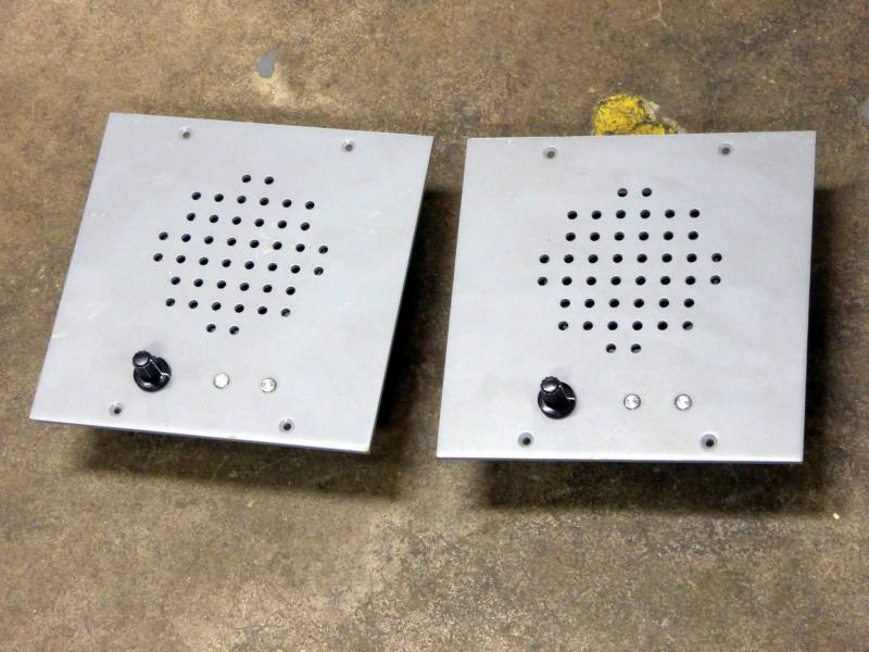 Light grey console mounting speaker panels with grills, volume control & LEDs