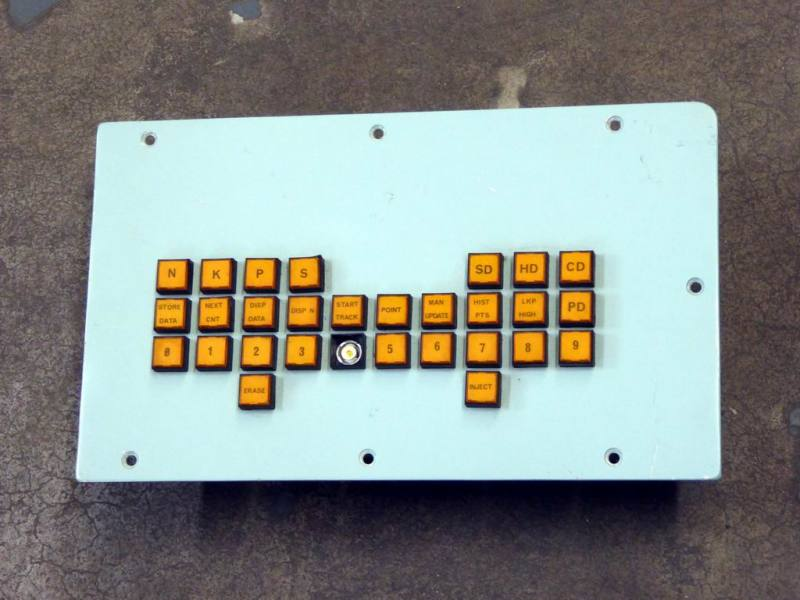 Practical British navy control panel with illuminated orange square buttons.