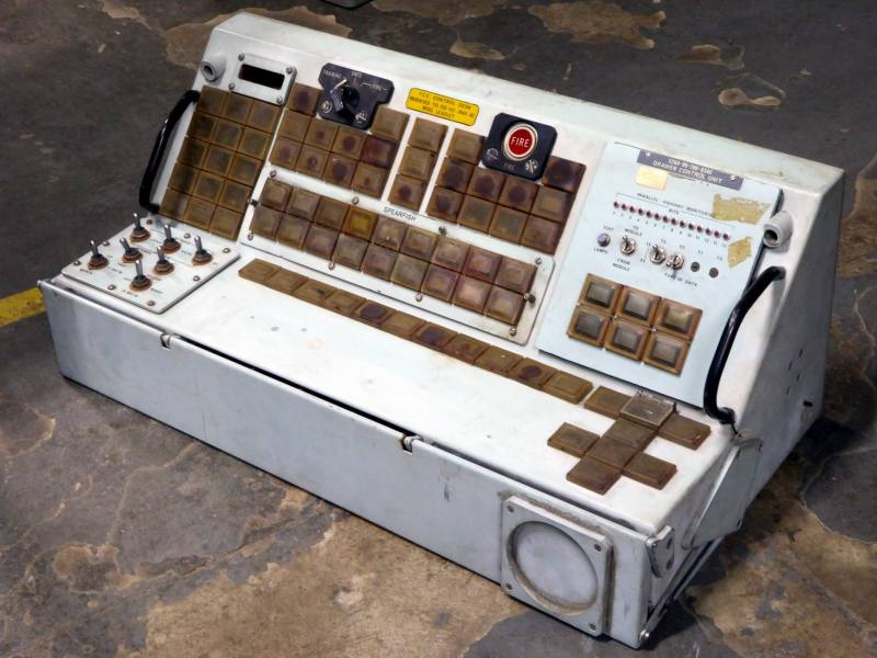 Navy submarine weapons control console with prominent Fire button & weapon specific rectangular buttons.