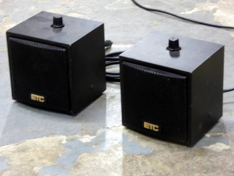 Small cube shaped black desktop speakers with volume control on top