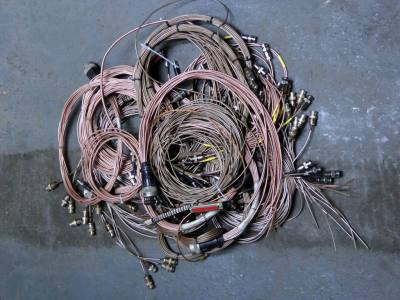 Crate of braided copper/goldy coloured sciency cables with knobbly metal connectors
