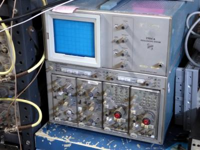 Large complex looking laboratory oscilloscope with many small switches & knobs