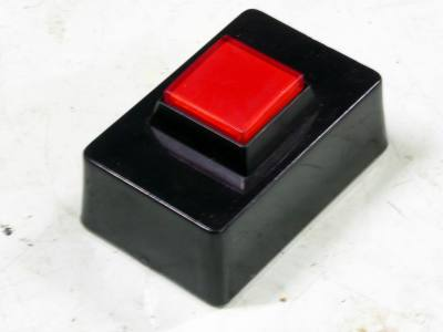 Small red desktop push button/switch on black base