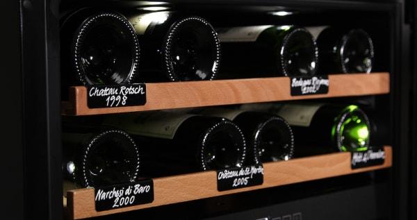 Vinetiketter på hyllor i vinlagringsskåp från mQuvée