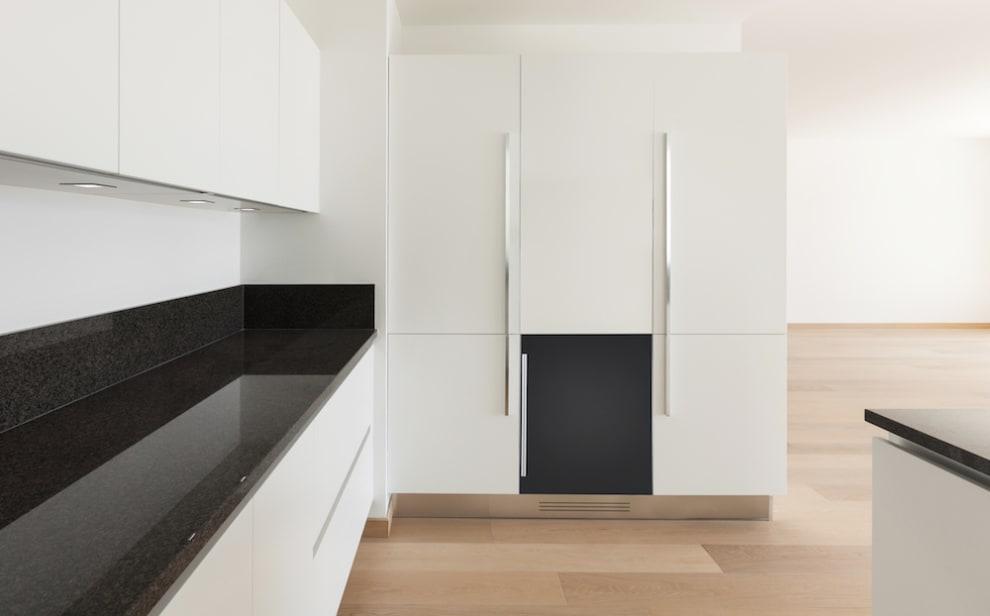 Litet svart vinlagringsskåp integrerat i vitt kök