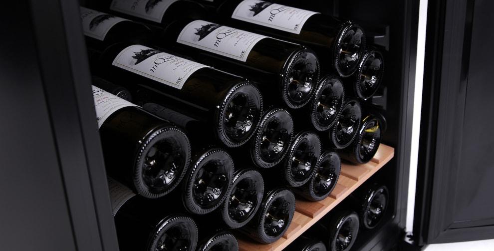 Flera liggandes vinflaskor i vinlagringsskåp