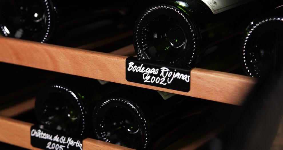 Vinetikett på hylla till svart robust vinlagringsskåp