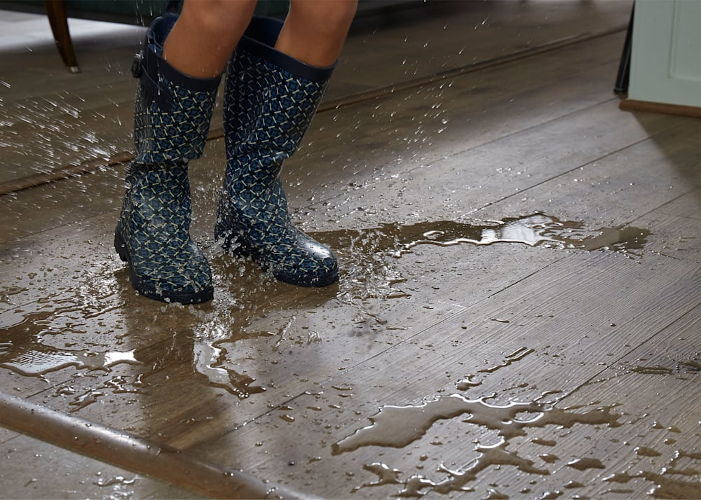 waterproof brown vinyl floor with water spilled. kid in rain boots.