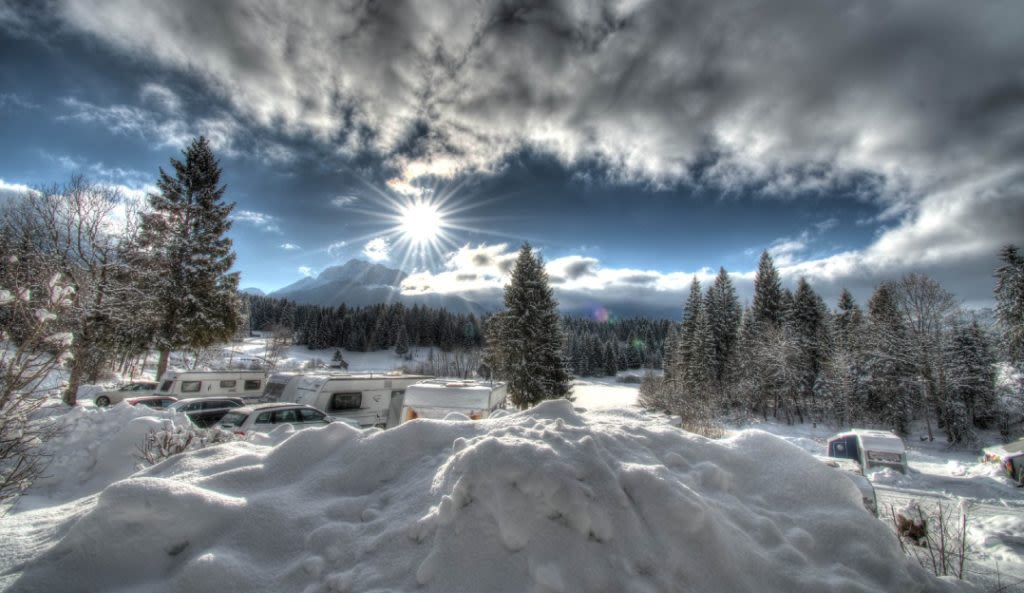 An image of an icy cold morning overlooking a camp site in the mountains, representing AWS Lambda cold starts.