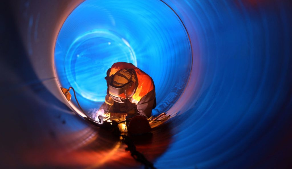 Pipe welding on the pipeline construction, representing the construction of a CICD pipeline for serverless applications using TravisCI.