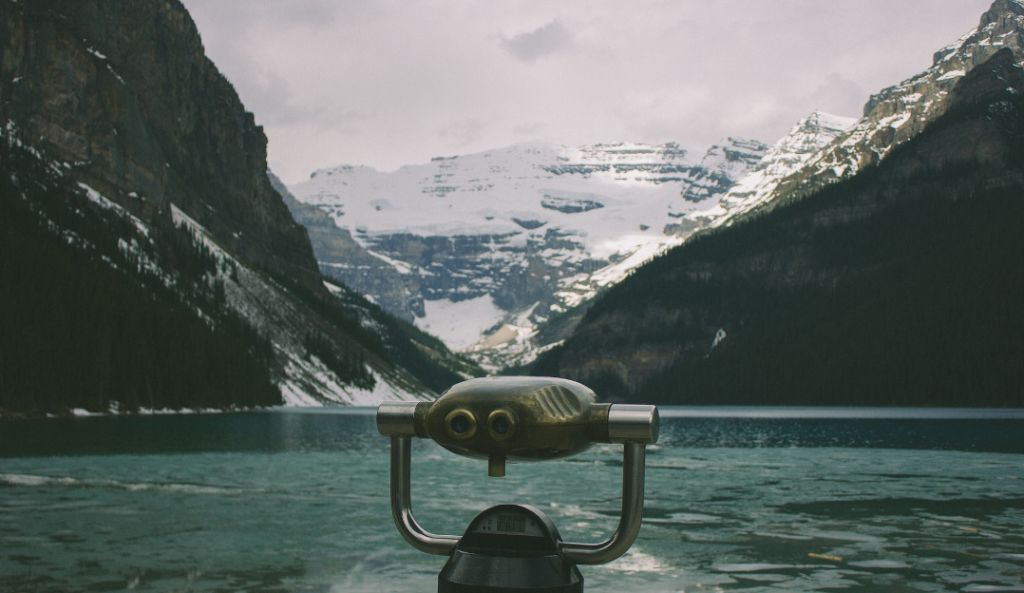 An image of binoculars and a winter landscape.