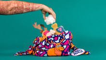 a pink knot wrap with a moose on with tattooed arm taking out bear soap