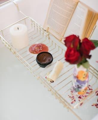 Bain avec un livre, une bougie, un trio de roses et des produits Lush Fresh & Flowers