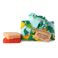 A colourful tengri wrap with an orange and leaves design and a brown tag with black text. Next to the wrap is a brown soap stacked on top of an orange, square piece of soap