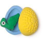 bomba de banho gigante de color azul e verde em forma de ovo com um  dinossauro verde dentro