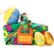 basket gift covered in green nature themed  material with products surrounding it