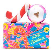 Una caja de regalo de navidad de color rosa y azul con una burbuja en forma de golosina y una bomba de baño arriba