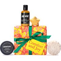 Una caja de regalo de color rojo y amarillo con un lazo verde y productos de cosmética alrededor