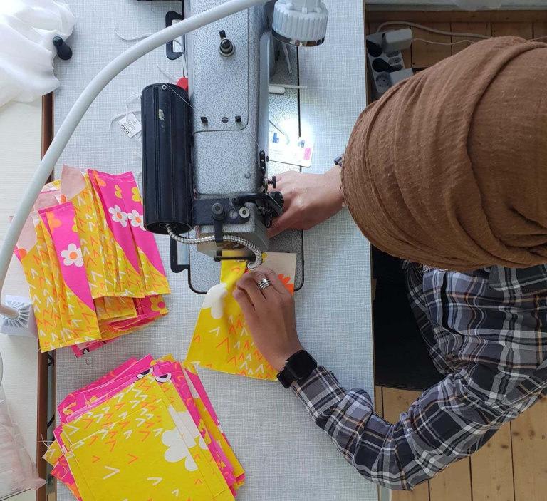Eine Näherin von Stitch by Stich stellt eine Schutzmaske aus einem Knot Wrap her an der Nähmaschine.
