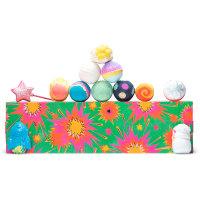Una caja de regalo rectangular de color verde con estrellas multicolores y bombas y burbujas de baño encima