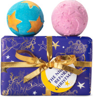 Un regalo de Navidad con envoltorio navideño y copos de nieve de color azul oscuro con 2 bombas de baño relajantes