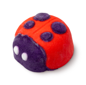 A ladybird shaped bubble bar. The ladybird is red with a purple face, purple spots and white eyes.
