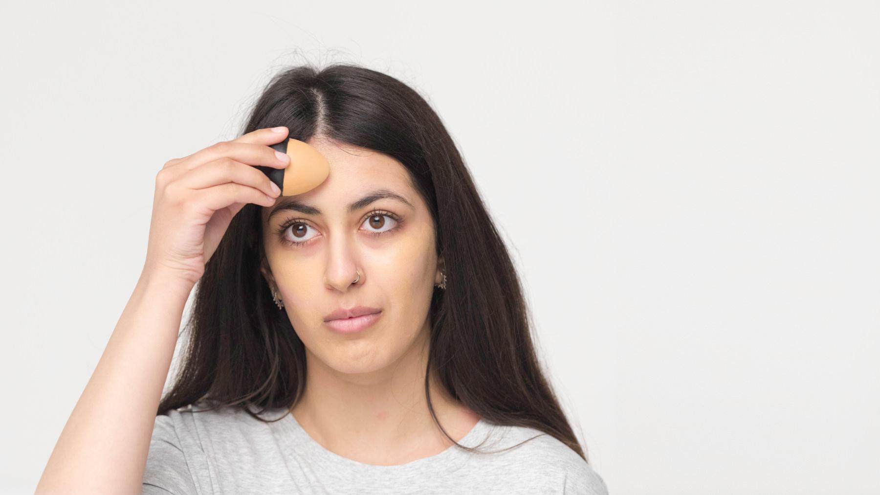 Una ragazza applica sul suo viso il fondotinta solido Slap Stick