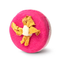 A dark pink shampoo bar with yellow rose petals in a flower shape in the middle.