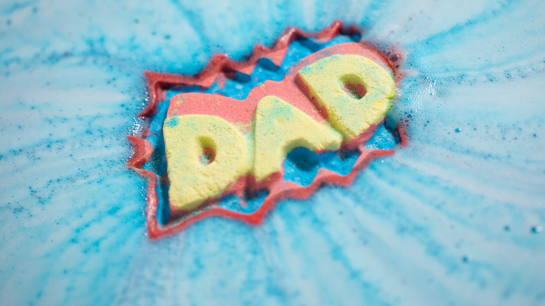 blue red and yellow bath bomb with 'dad' written on it in foam