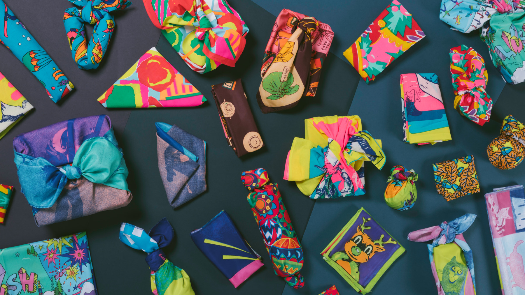 A selection of gifts wrapped in a variety of colourful knot wraps