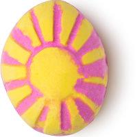 Eine pinke Badebomb in der Form eines Eies mit gelben Streifen