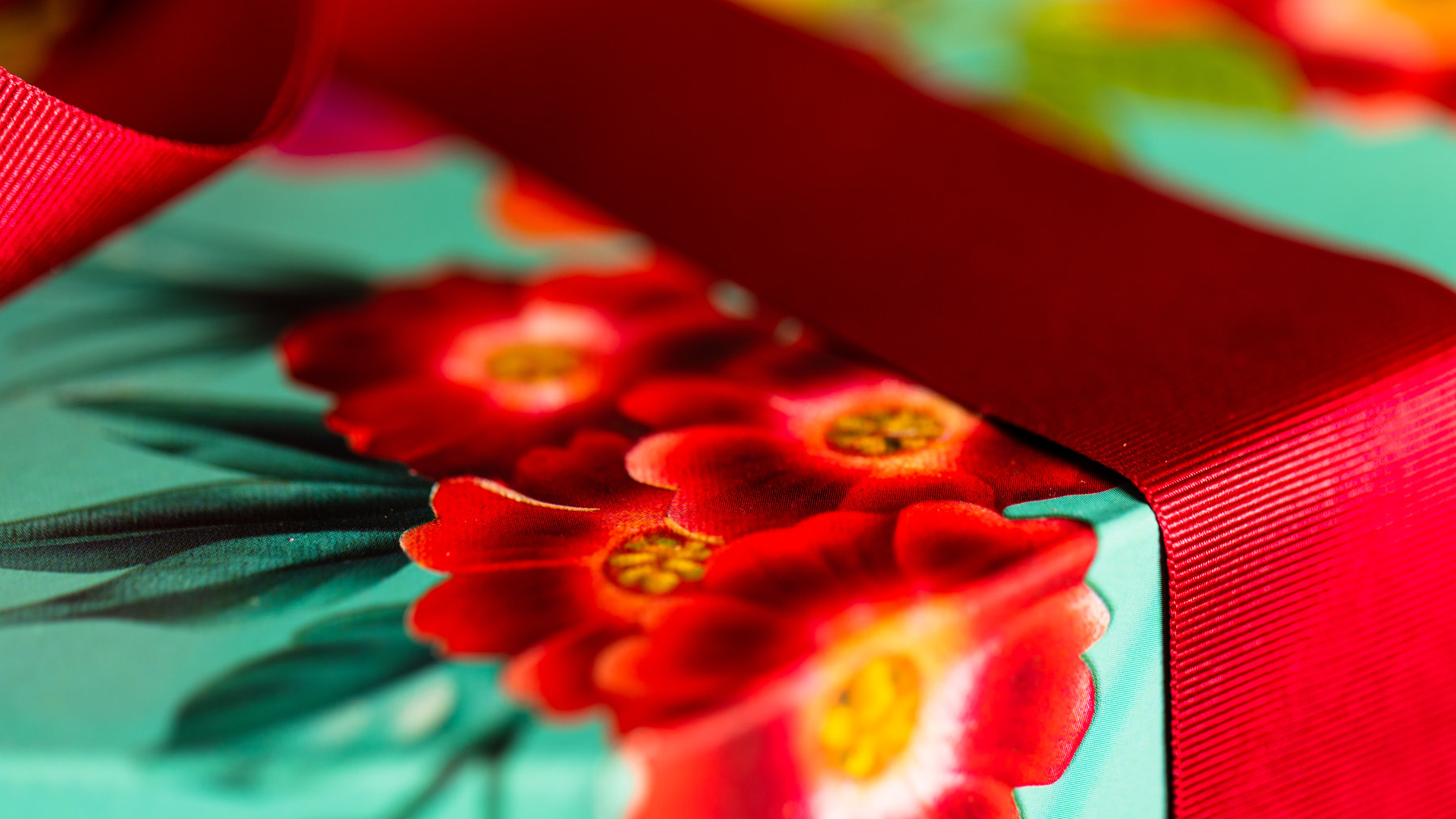 A close up image of a jewel coloured, floral designed gift box with a red ribbon