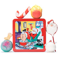 sleeping santa tin with christmas themed products surrounding it including bubble bars bath bombs and a bath oil on a white back ground