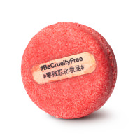 A round, red shampoo bar with a wooden stick in the centre that has #BeCrueltyFree printed on it