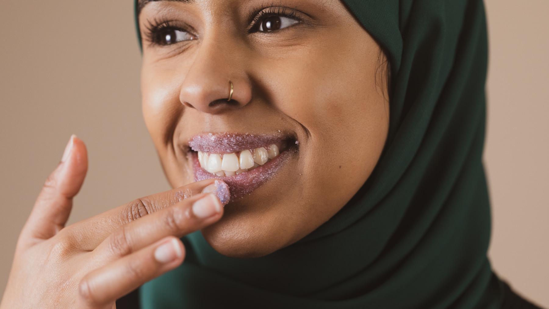 A person applying a purple sugar lip scrub to their lips while smiling