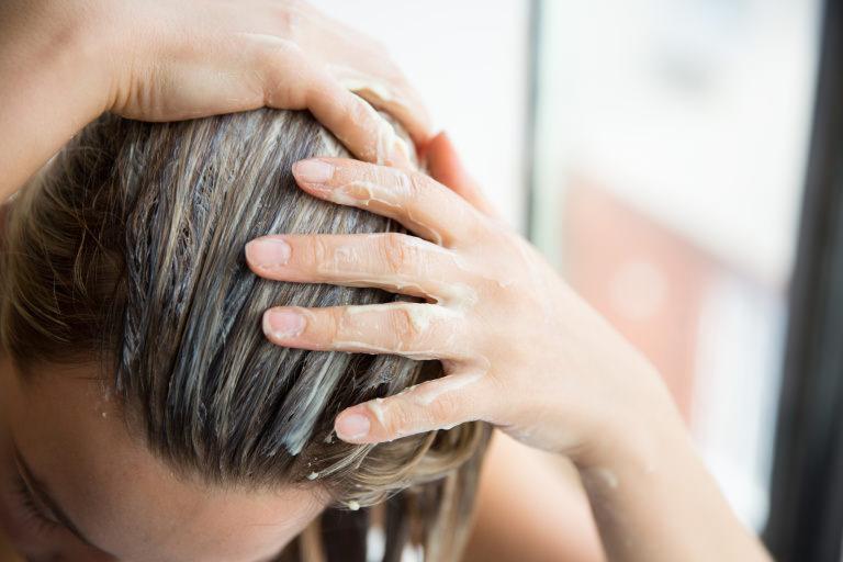 Una ragazza applica un prodotto per la cura dei capelli biondi, chiari o bianchi
