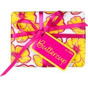 Ein Geschenkspackerl verpackt in weißes, mit gelb-pinken Blumen dekoriertes Geschenkspapier