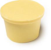 Eine feste, gelbe Creme in Form eines Lush Blackpots