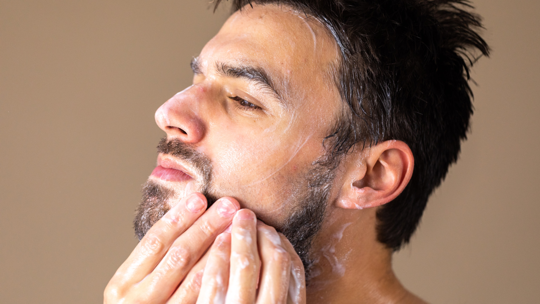 A man applying product on her face