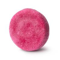 A round, bright pink shampoo bar