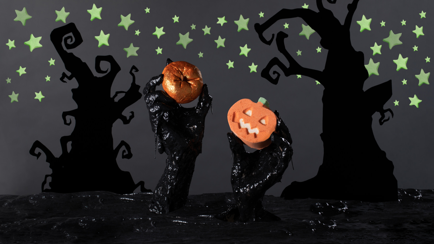 a pair of hands covered in black slime holding two pumpkin products