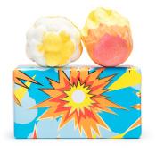 Un regalo de color azul y naranja con 2 bombas de baño encima en un fondo blanco