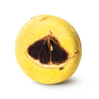 A round, bright yellow shampoo bar with a dehydrated segment of lemon in the center