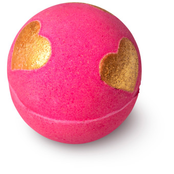 pink coloured bath bomb with golden glittery hearts on it