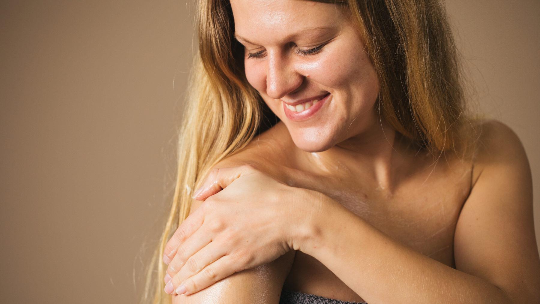 una mujer aplicando el hidratante corporal pansy en sus brazos